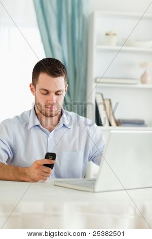 Young businessman texting on his cellphone in his homeoffice