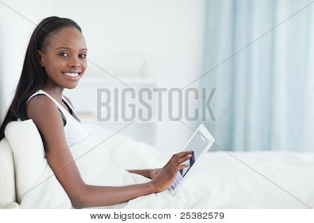 Beautiful woman using a tablet computer in her bedroom