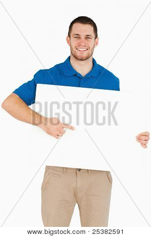 Smiling young salesman pointing at banner in his hands against a white background