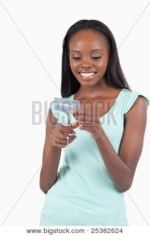 Happy smiling young female destroying credit card against a white background