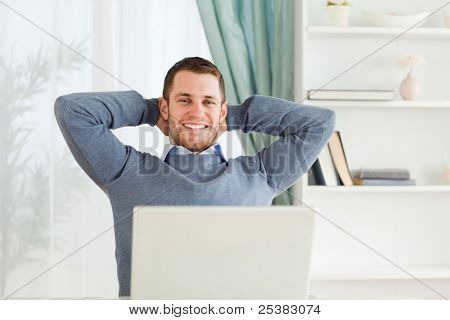 Smiling young businessman leaning back in his home office