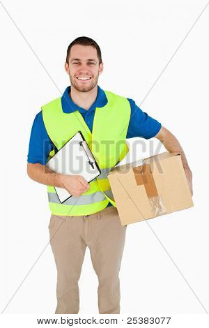 Smiling young delivery man with parcel and delivery note against a white background