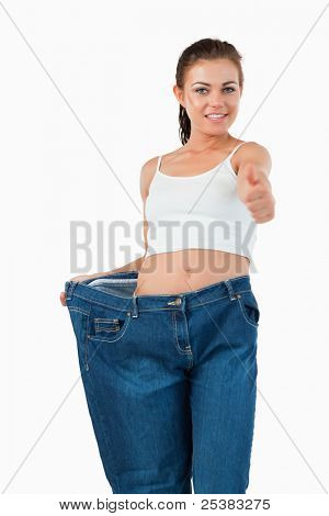 Portrait of a fit woman wearing too large jeans with the thumb up against a white background