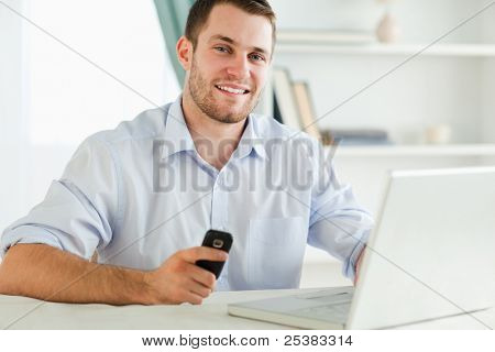 Smiling young businessman holding his cell while typing on his laptop