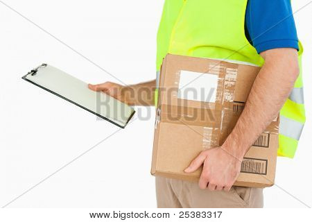 Side view of young delivery man with delivery note and parcel against a white background