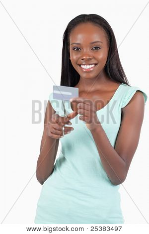 Happy smiling woman destroying her credit card against a white background