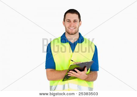 Smiling young delivery man completing delivery note against a white background