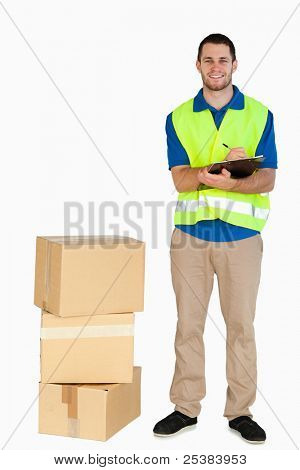 Smiling young delivery man filling in delivery note against a white background
