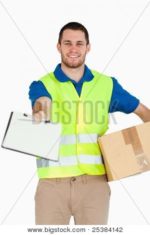 Smiling young delivery man with packet asking for signature against a white background