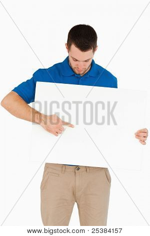 Young salesman pointing at banner he is holding against a white background