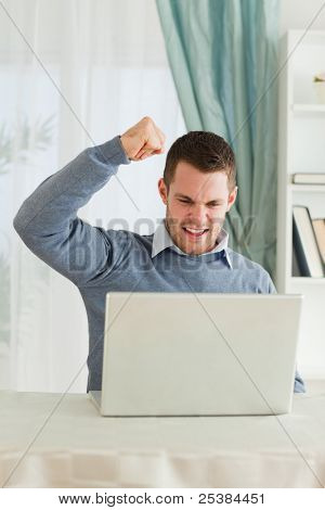 Young businessman with raised fist in his home office