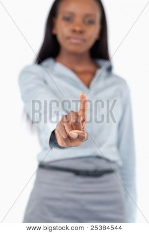 Portrait of a young businesswoman touching an invisible screen against a white background