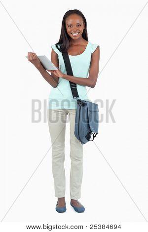 Sonriente joven estudiante con su libreta de apuntes sobre fondo blanco