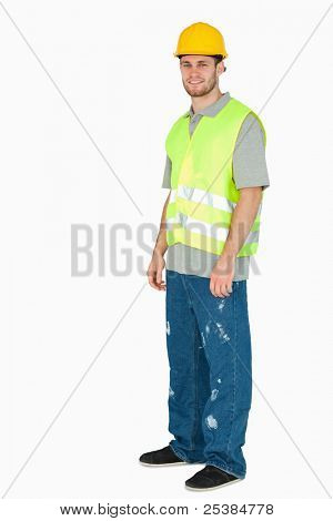 Side view of smiling young construction worker against a white background