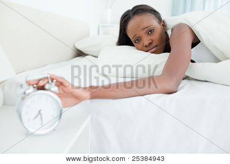 Tired young  woman switching off her alarm clock in her bedroom
