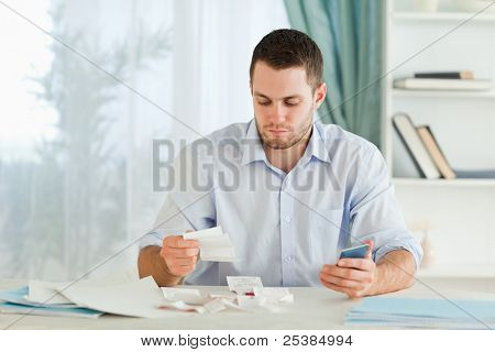 Young businessman with pocket calculator checking invoices