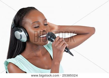 Young woman enjoys singing against a white background