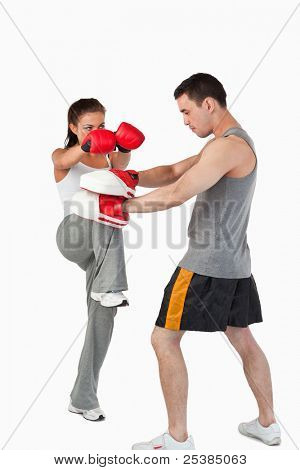 Female kick boxer practicing her knee technique against a white background