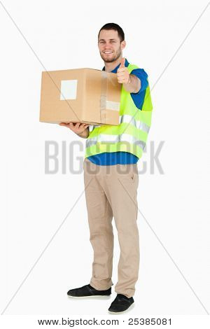 Smiling young delivery man giving approval while holding a parcel against a white background