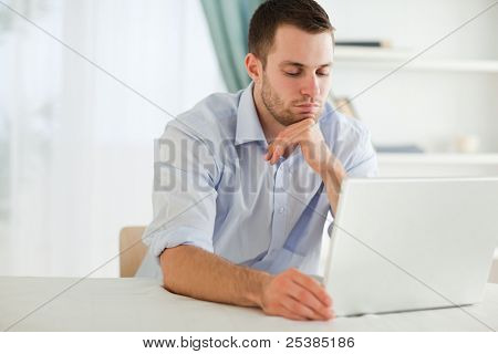 Young businessman reading an e-mail on his laptop