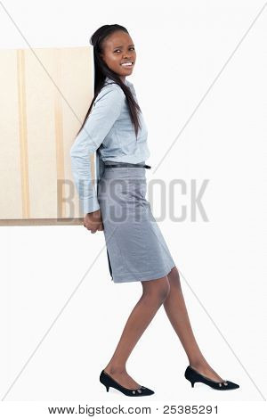 Portrait of a young businesswoman pushing a panel with her back against a white background