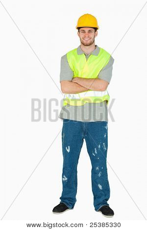 Smiling young construction worker with arms folded against a white background