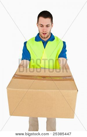 Surprised looking delivery man handing over parcel against a white background