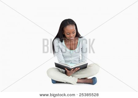 Young woman sitting cross-legged on the floor reading against a white background
