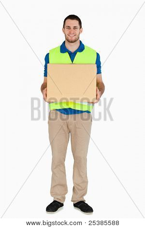 Smiling young delivery man carrying a parcel against a white background