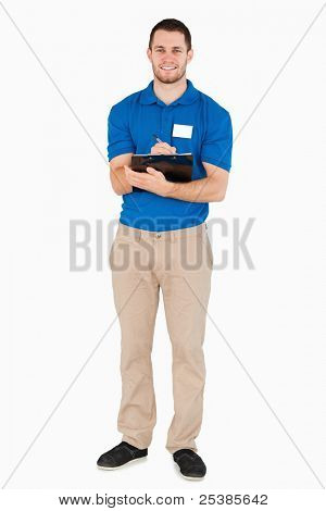 Smiling young salesman making a survey against a white background
