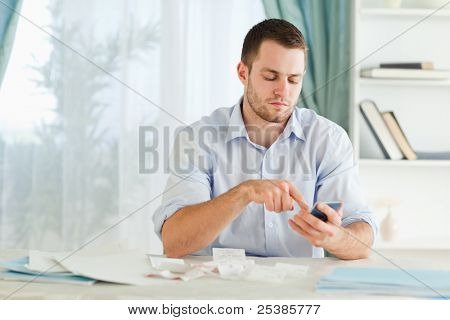 Young businessman typing on his calculator