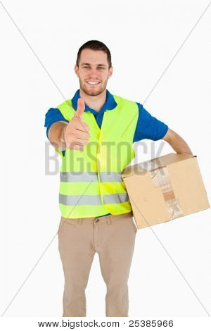 Smiling young delivery man with parcel giving thumb up against a white background
