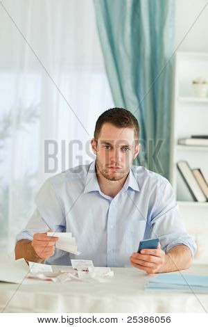 Serious looking young businessman doing accounting
