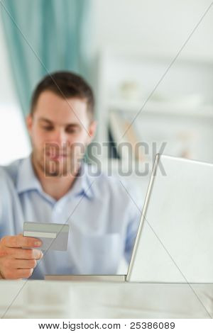 Young businessman with notebook and credit card in his home office