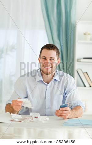 Young businessman with hand calculator checking invoices