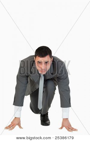 Portrait of a businessman in the starting blocs against a white background