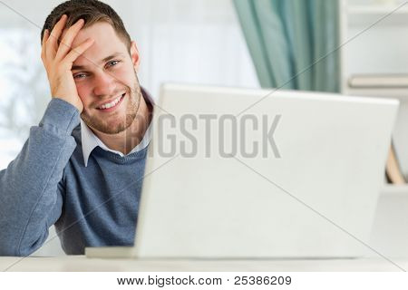 Smiling young businessman tired in his homeoffice