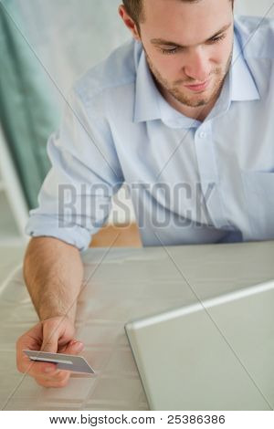 Young businessman with credit card on his laptop