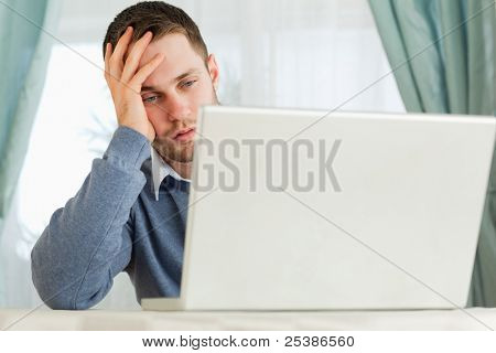 Young businessman annoyed by his laptop in his homeoffice