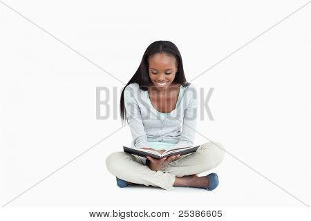 Young woman sitting on the floor reading a book against a white background