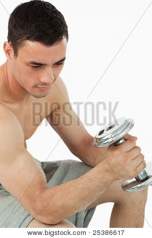 Young male pumping iron against a white background