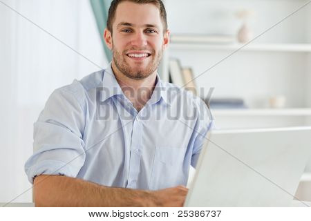 Smiling young businessman with rolled up sleeves in his home business