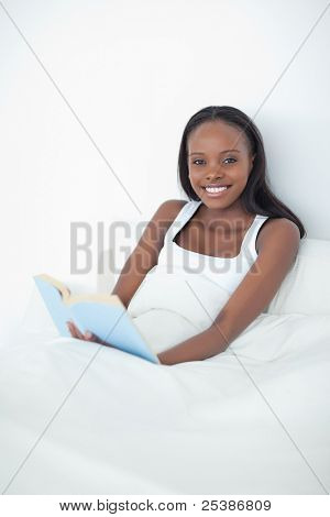 Portrait of a happy woman holding a book in her bedroom