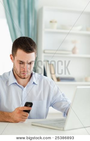 Young businessman reading text message in his home office