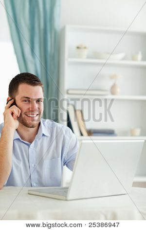 Smiling young businessman in his home office on the phone