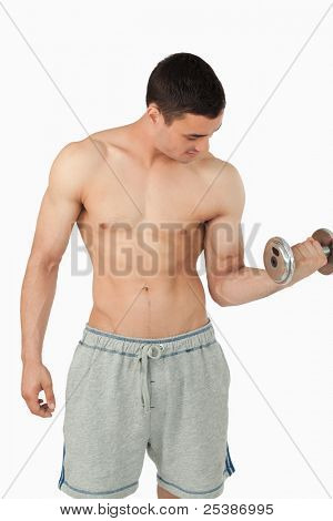 Sporty male lifting weights against a white background