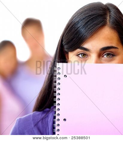 Female student covering her face wih a notebook - isolated over a white background