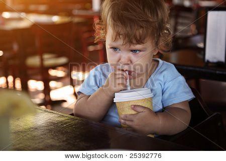 Lindo niño triste agua potable en el restaurante.