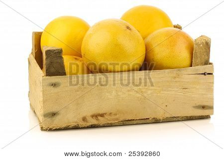 yellow and red grapefruit in a wooden box