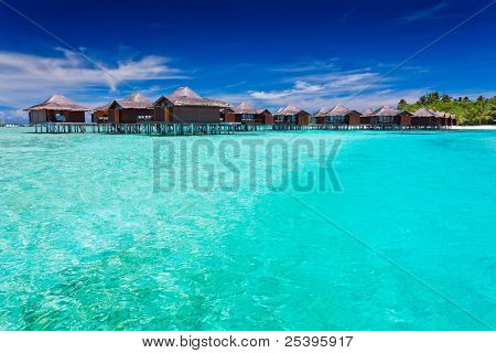 Overwater bungallows in blue lagoon around tropical island